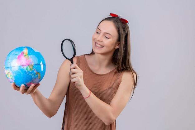 Junge schöne frau mit sonnenbrille auf kopf halten und durch vergrößerungsglas auf globus mit interesse lächelnd stehend über weißem hintergrund schauen