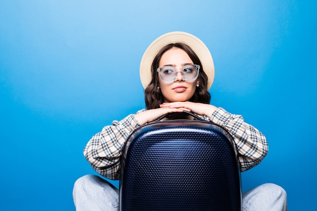 Junge schöne frau mit sonnenbrille und strohhut mit koffer, der pass vor flugwarteflugzeug hält