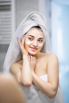 Junge schöne frau mit weißem hemd, die gesichtscreme auf ihre schöne gesunde haut im badezimmer aufträgt