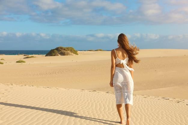 Junge schöne frau mit weißem kleid, das in den wüstendünen während des sonnenuntergangs geht. mädchen, das auf goldenem sand auf corralejo dunas, fuerteventura geht.