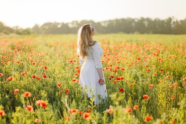 Junge schöne frau mit weißem kleid posiert in einem mohnfeld