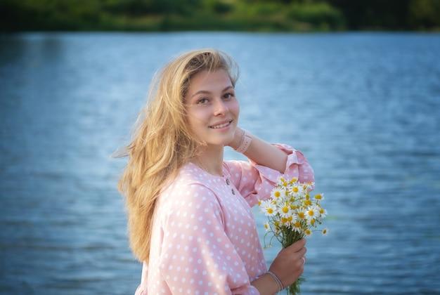 Junge schöne frau mit weißen gänseblümchen am flussufer