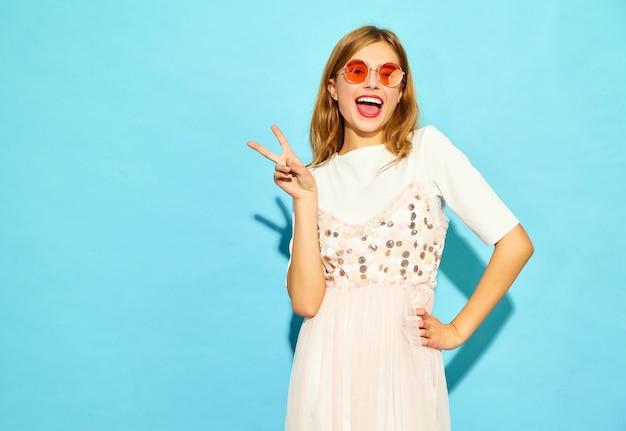 Junge schöne frau. modische frau in der zufälligen sommerkleidung blinzelnd in der sonnenbrille. lustiges modell lokalisiert auf blauer wand
