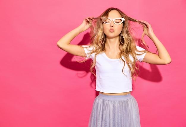 Junge schöne frau modische frau in der zufälligen sommerkleidung in der gefälschten stützensonnenbrille. positive weibliche gefühlgesichtsausdruck-körpersprache. lustiges modell, das mit ihrem haar auf pu spielt