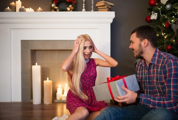 Junge schöne frau packte ihren kopf für das unerwartete geschenk ihres mannes für neujahr und weihnachten, das im wohnzimmer, nahe einem dekorativen kamin mit kerzen und weihnachtsbaum sitzt