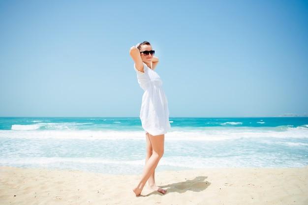 Junge schöne frau posiert am strand