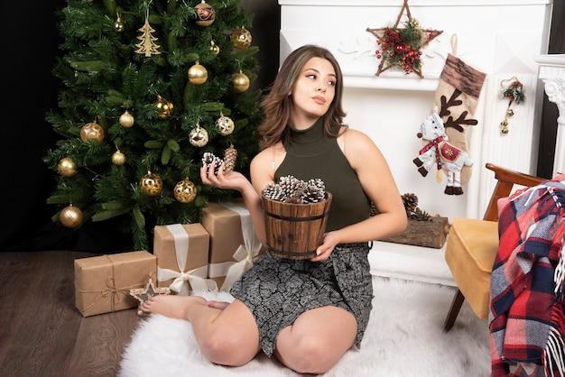 Junge schöne frau posiert mit korb mit tannenzapfen in der nähe des weihnachtsbaums
