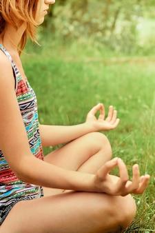 Junge schöne frau praktiziert yoga auf der sonnigen wiese. aktiver lebensstil. schönheitsfrau, die yoga macht gesundes und yoga-konzept. fitness und sport