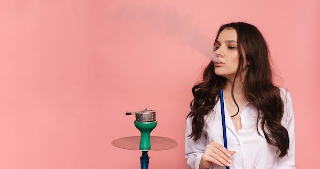 Junge, schöne frau raucht eine wasserpfeife, shisha. es erzeugt rauch aus seinem mund. das vergnügen zu rauchen. platz für ihren text.