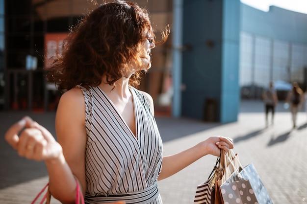 Junge schöne frau shopaholic verlässt das einkaufszentrum mit einer packung taschen mit einkäufen.