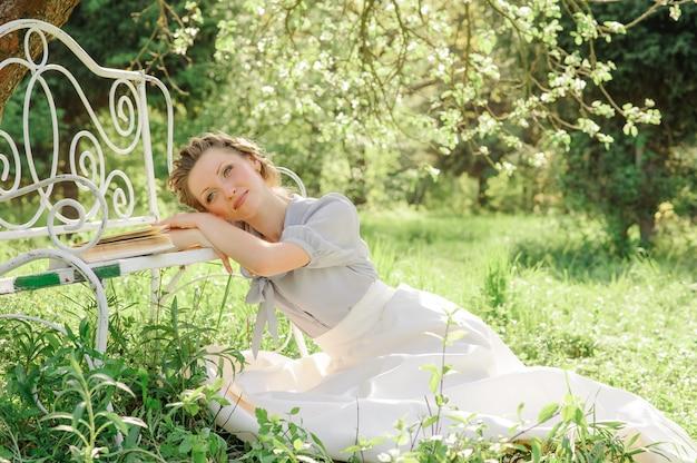 Junge schöne frau sitzt auf dem boden nahe einer bank auf einer landschaft von blühenden apfelbäumen. auf der bank liegt ein buch. das mädchen träumt von etwas.