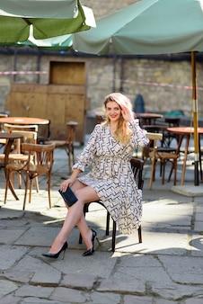 Junge schöne frau sitzt auf einem stuhl auf einer restaurantterrasse.