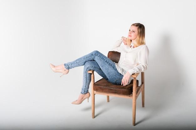 Junge schöne frau sitzt auf einem stuhl