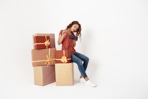 Junge schöne frau sitzt auf großer geschenkbox, die kleinere öffnet