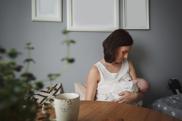 Junge schöne frau stillt ein kleines baby in einem gemütlichen raum