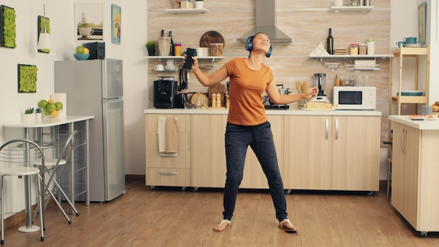 Junge schöne frau tanzt beim musikhören in blauen drahtlosen kopfhörern in der küche. energiegeladene, positive, fröhliche, lustige und süße hausfrau, die alleine im haus tanzt. unterhaltung und freizeit