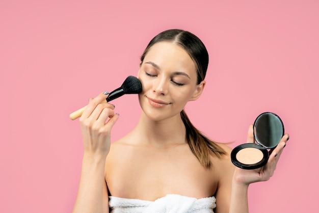 Junge schöne frau trägt natürliches puder-make-up auf einer rosa wand auf.