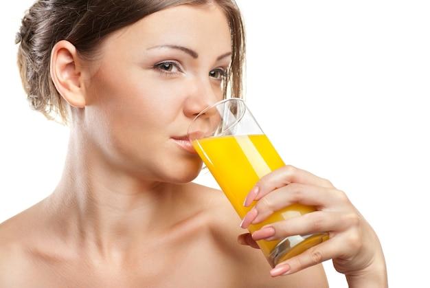 Junge schöne frau trinkt orangensaft isoliert auf weißem hintergrund