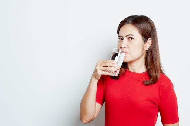 Junge schöne frau trinkt wasser aus einem glas