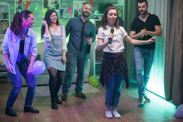 Junge schöne frau, umgeben von ihren freunden, die karaoke auf der party machen.