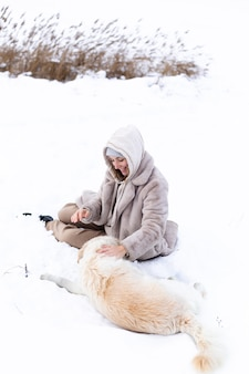 Junge schöne frau und ihr golden retriever hund haben spaß im winter in