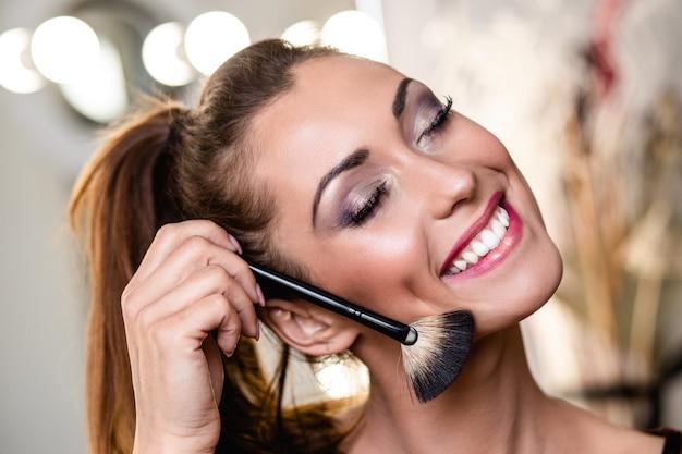 Junge schöne frau und professionelle schönheit bilden künstler-vlogger oder blogger, die make-up-tutorial aufzeichnen, um sie auf der website oder in sozialen medien zu teilen.