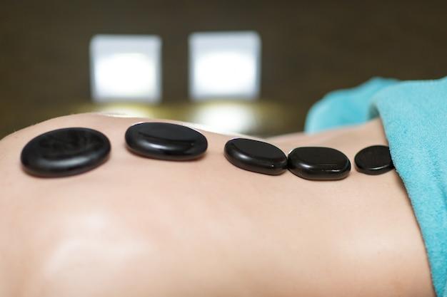 Junge schöne frau und steinmassage im beauty spa