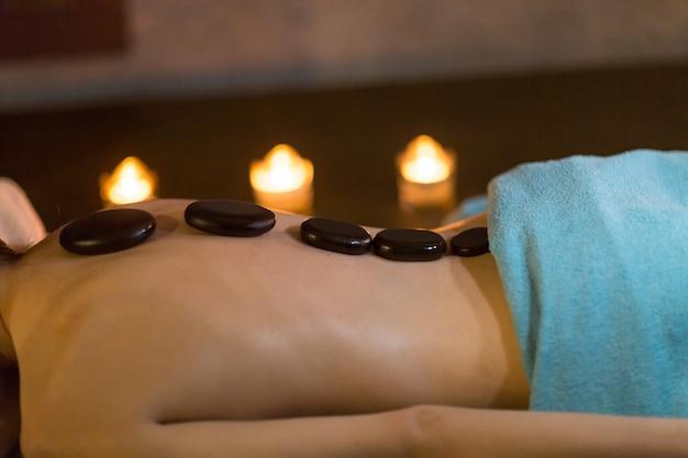 Junge schöne frau und steinmassage im schönheits-spa mit kerzenlicht