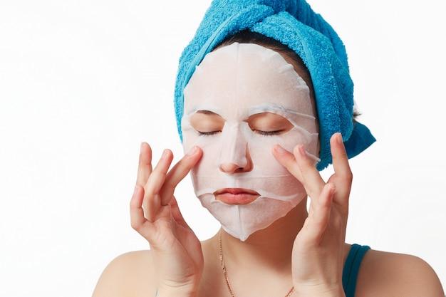 Junge schöne frau verwendet eine kosmetische gesichtsmaske aus stoff mit einem handtuch um den kopf gewickelt.