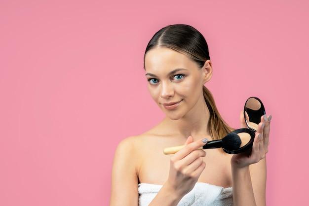 Junge schöne frau verwendet natürliches puder-make-up auf einer rosa wand.