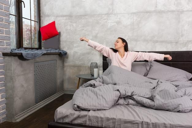 Junge schöne frau wachte auf und streckte sich, während sie im bett saß und einen schlafanzug im schlafzimmer im loft-stil mit grauen farben trug