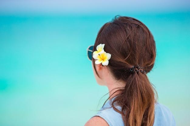 Junge schöne frau während der tropischen strandferien. genießen sie ihren urlaub allein am strand mit frangipani-blüten im haar