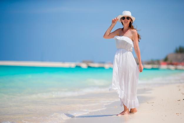 Junge schöne frau während der tropischen strandferien. glückliches mädchen im weißen kleid genießen ihre sommerferien