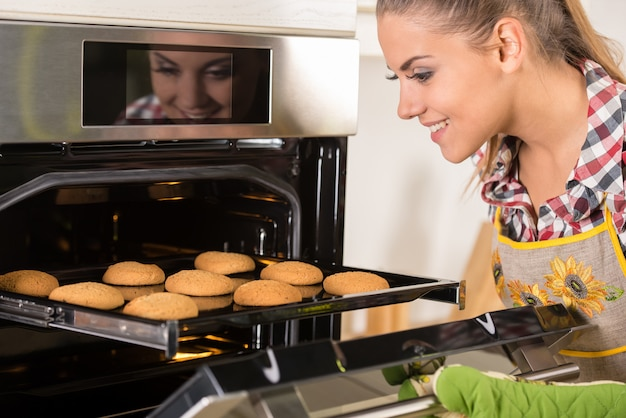 Junge schöne frau zieht kekse aus dem ofen.