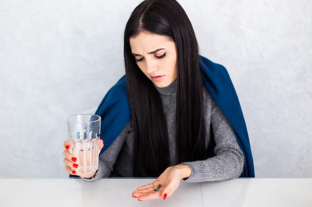 Junge schöne frau zu hause auf weißem tisch, der sich unwohl fühlt und als symptom für erkältung oder bronchitis hustet. gesundheitskonzept.