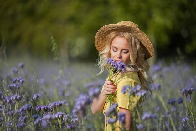 Junge schöne fraublondine in einem hut geht durch ein feld der lila blumen. sommer. frühling.