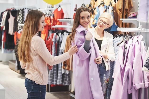 Junge schöne frauen auf dem wöchentlichen stoffmarkt. der filialleiter hilft dem käufer. beste freunde, die ihre freizeit teilen, spaß haben und einkaufen.