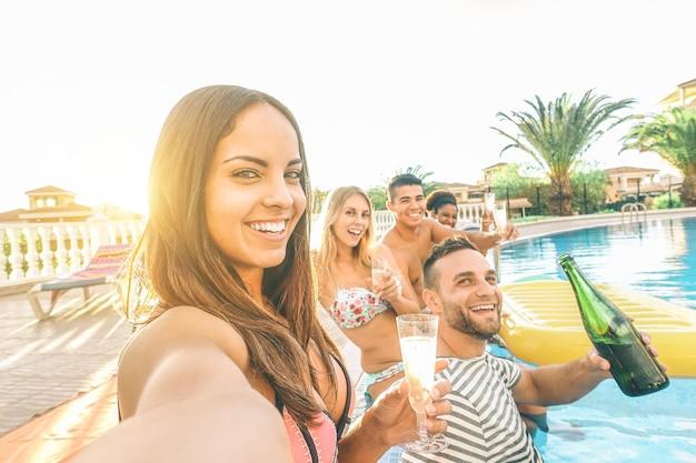 Junge schöne frauen, die ein selfie mit ihren freunden machen, die poolparty machen, champagner trinkend
