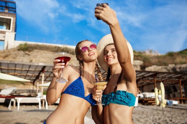 Junge schöne frauen in der badebekleidung lächelnd, selfie am strand machend
