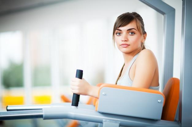 Junge schöne frauen in der sportbekleidung, die training mit fitnessgerät für beine mit leerem fitnessstudio macht