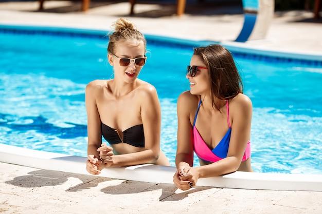 Junge schöne frauen lächelnd, sprechend, entspannend im schwimmbad.