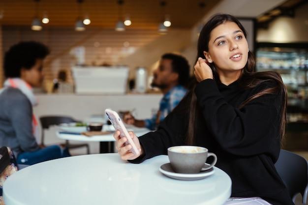 Junge schöne frauen mit smartphone, charmante studentin, die im café sitzt