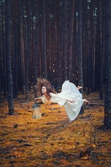 Junge schöne frauenfee, die im wald mit laterne fliegt. levitation, magie