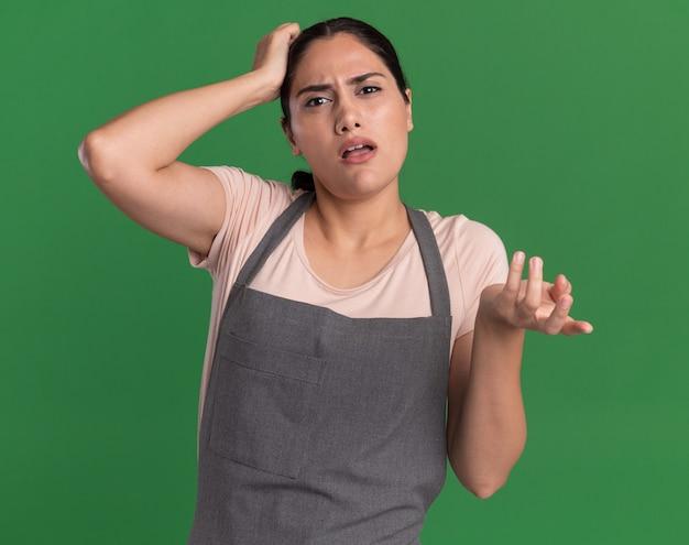 Junge schöne friseurin in der schürze, die vorne mit verwirrendem ausdruck mit hand auf ihrem kopf für fehler betrachtet, der über grüner wand steht