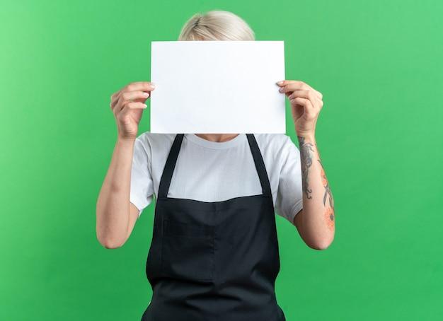 Junge schöne friseurin in uniform bedeckt gesicht mit papier auf grünem hintergrund isoliert