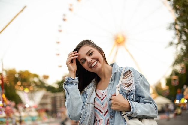 Junge schöne fröhliche brünette frau im trendigen jeansmantel, der über riesenrad im vergnügungspark steht, glücklich schaut und ihr haar glättet