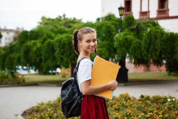 Junge schöne fröhliche studentin, die lächelt und ordner draußen hält.
