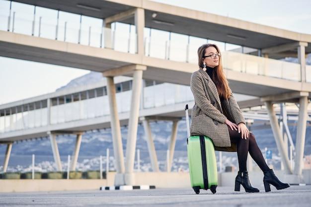 Junge schöne geschäftsfrau am internationalen flughafen mit koffer