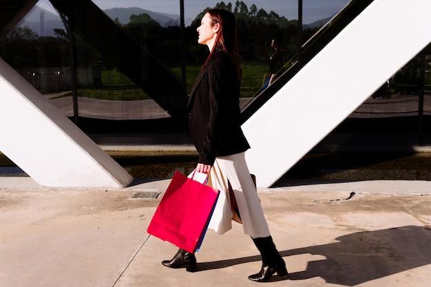 Junge schöne geschäftsfrau auf der straße im einkaufsviertel beim einkaufen mit farbigen taschen zu fuß