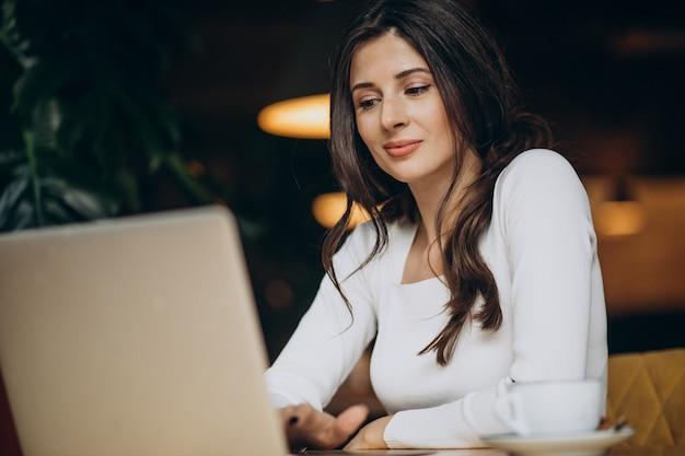 Junge schöne geschäftsfrau, die am computer in einem café arbeitet